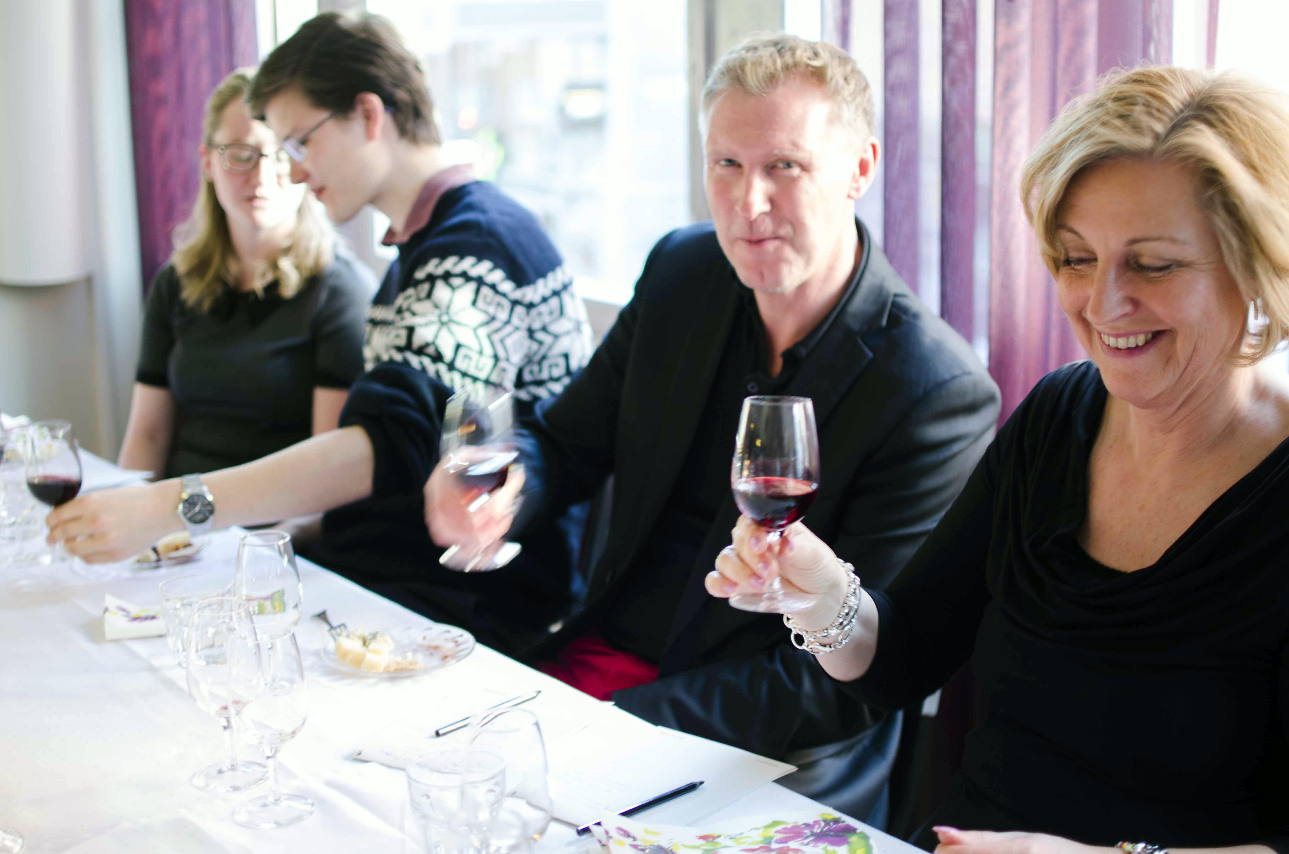 Vinprovning med några glada deltagare som provar rött vin
